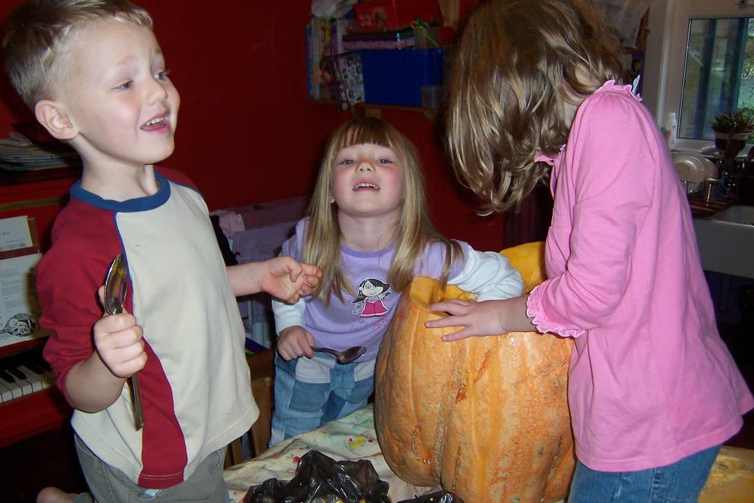 children scooping out a pumpkin
