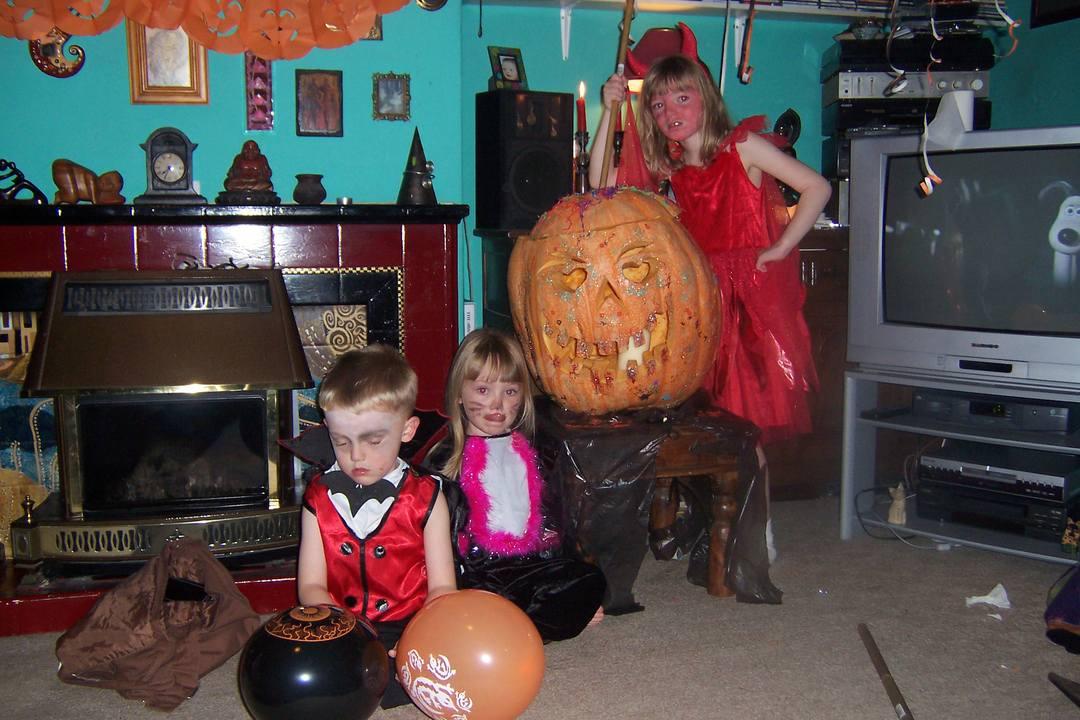 Children in fancy dress with pumpkin