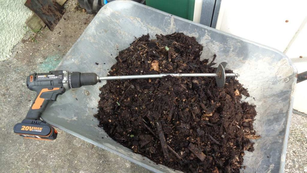 Wheelbarrow filled with compost, cordless drill with auger.